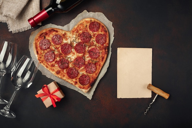 Heart shaped pizza with mozzarella, sausagered and wine bottle, corkscrew, wineglass . Premium Photo