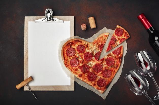 ハート型のピザ、モッツァレラチーズ、ソーセージ、ワインボトル、2つのワイングラス、さびた背景にタブレット Premium写真