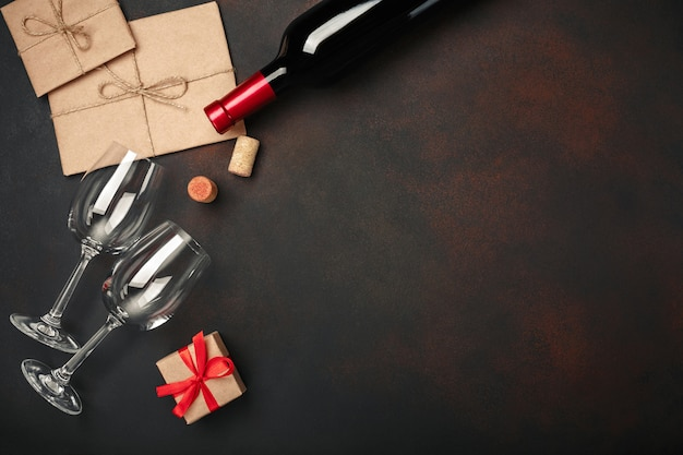 Heart shaped pizza with mozzarella, sausagered, wine bottle, two wineglass, gift box on rusty background Premium Photo