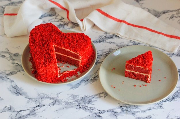 Heart shaped red velvet cake on marble table slice aside Free Photo