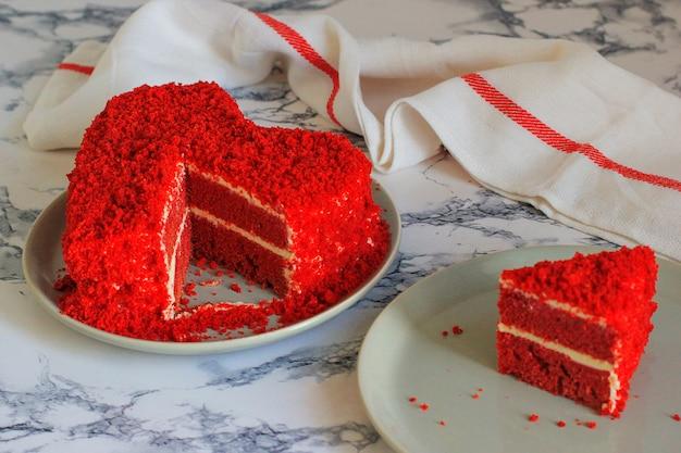 Heart shaped red velvet cake on marble table slice aside Free Photo