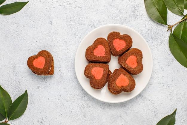 ハート型の明るい背景に冷凍ラズベリーとバレンタインクッキー 無料写真