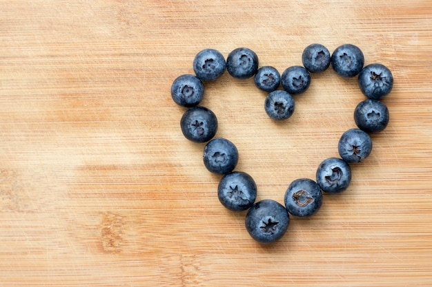 Heart symbol formed with blueberries on wooden Premium Photo