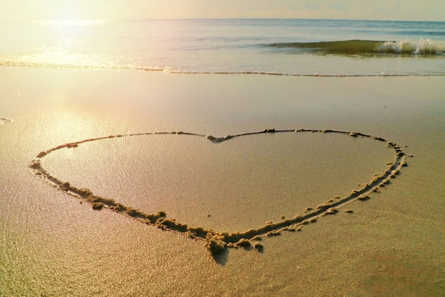 Heart with the waves beat at the beach and sunlight in the summer morning Premium Photo