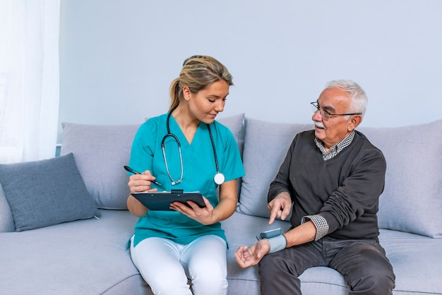 Heart work. attentive caregiver using tonometer while elder man having breath problem Premium Photo