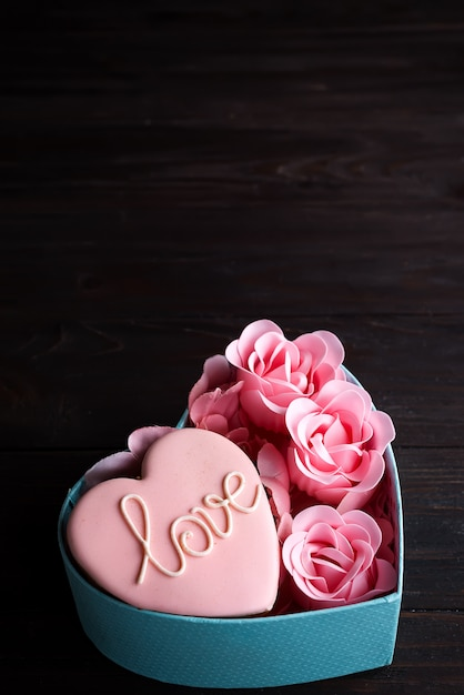 Hearts cookies in heart blue box with rose on dark wooden