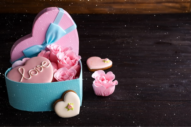 Hearts cookies in heart blue box with rose on dark wooden background
