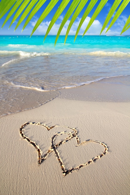 Hearts in love written in caribbean beach sand Premium Photo