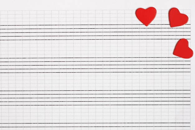 Hearts of red paper lie on a clean music notebook. the concept of music and love. Premium Photo