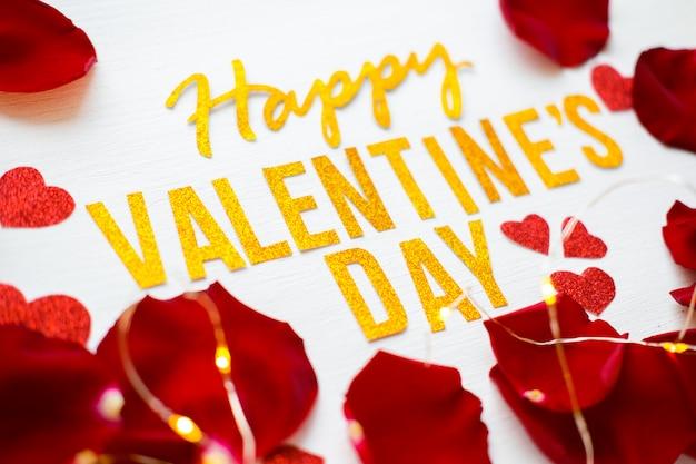 Счастливый день святого валентина текст поздравительных открыток с лепестками красной розы и heartson белый деревянный фон. романтика и любовь концепция Premium Фотографии