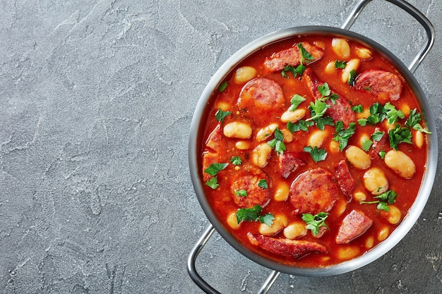 ソーセージ、ハーブ、スパイスを金属製のキャセロールにトマトソースで煮込んだボリュームたっぷりの豆のシチュー Premium写真