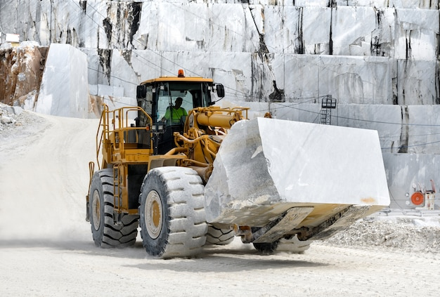 Heavy duty front end loader moving a large block of white carrara marble in an open cast mine or qu