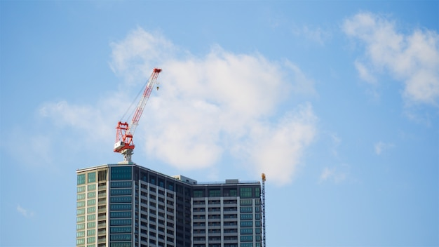 Heavy equipment crane over skyscraper building site in bright blue sky and cloud at the morning day, use for lift and transport object to the place Premium Photo