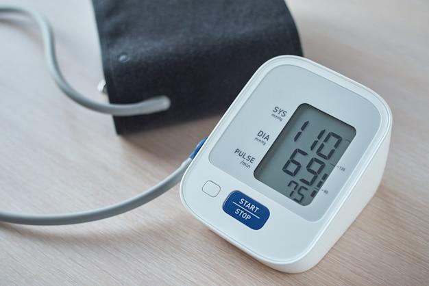 Монитор кровяного давления цифров на таблице, крупном плане. helathcare и медицинская концепция Premium Фотографии