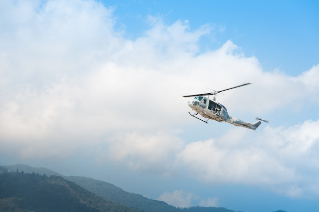 飛行中のヘリコプター、青い空を背景 Premium写真