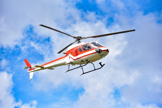 Helicopter rescue helicopter flying on sky / white red fly helicopter on blue sky with clouds good air bright day Premium Photo