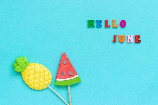 Hello june, pineapple and watermelon lollipops on stick. concept vacation or holidays Premium Photo