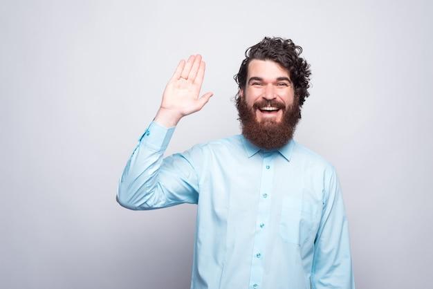 こんにちは人々、カジュアルな敬礼ジェスチャーでひげを生やした男の笑顔。 Premium写真