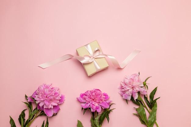 こんにちは春。牡丹と白とピンクのテーブルにギフトの創造的な花の組成 Premium写真