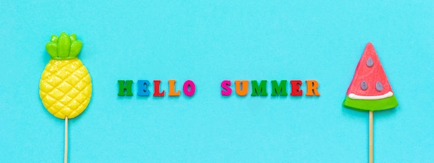 Hello summer colorful text, pineapple and watermelon lollipops concept vacation or holidays banner Premium Photo