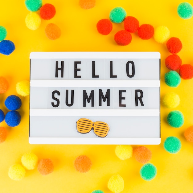 Hello summer light box with colorful small pom pom balls on yellow background Free Photo
