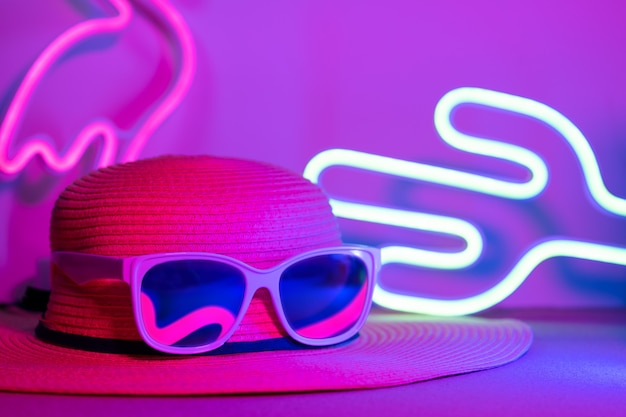 Hello summer with hat and sunglasses refection flamingo neon light with cactus on  pink and blue light Premium Photo