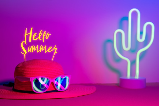 Hello summer with hat and sunglasses refection neon light with cactus on  pink and blue on table Premium Photo