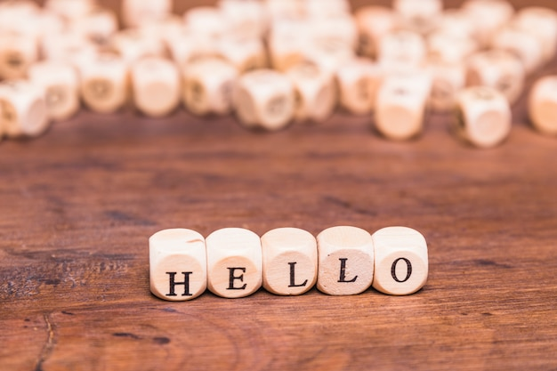 Hello word made with dices on wooden desk Free Photo