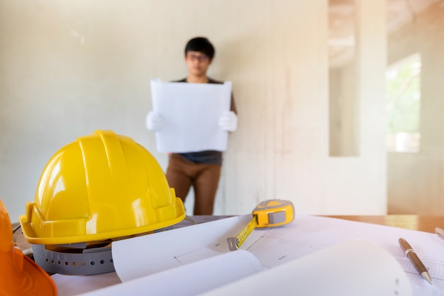 Helmet and blueprint on desk in front of  engineer or architect. Premium Photo