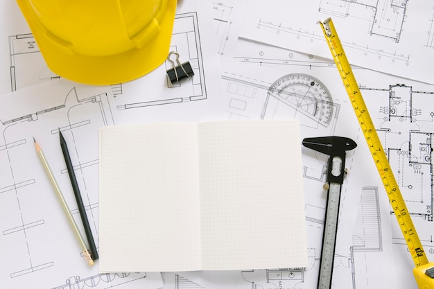 Helmet and drafting supplies on blueprints Free Photo