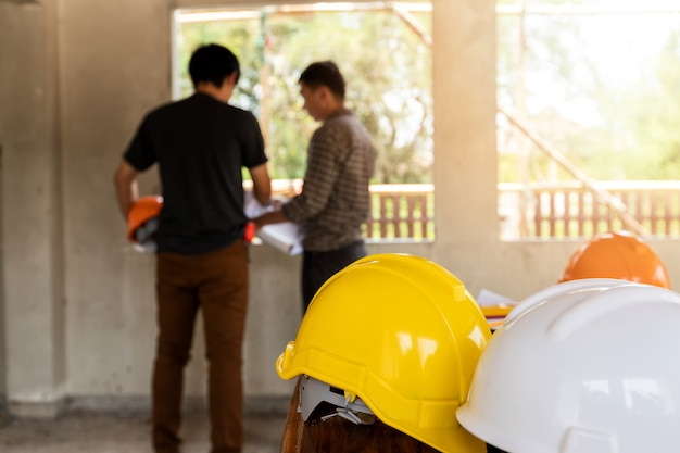 Helmets on desk in front of  engineer or architect discussing in construction site Premium Photo