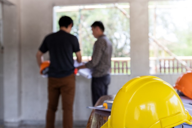 Helmets on desk in front of  engineer or architect discussing with foreman Premium Photo