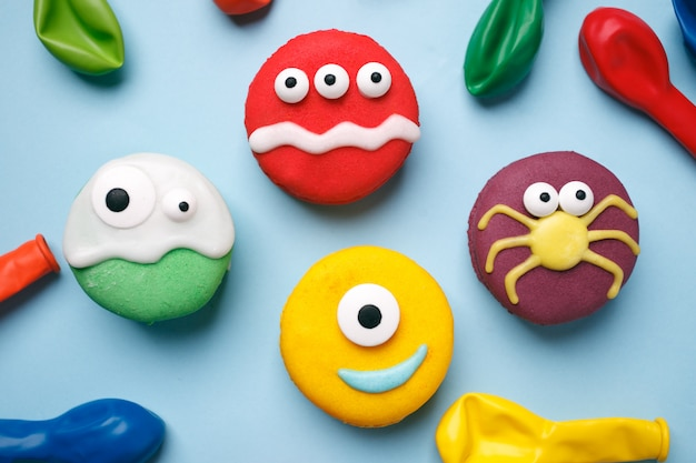 Heloween dessert: funny monsters made of biscuits macaroon with icing and candy eyes close-up on the table. Premium Photo