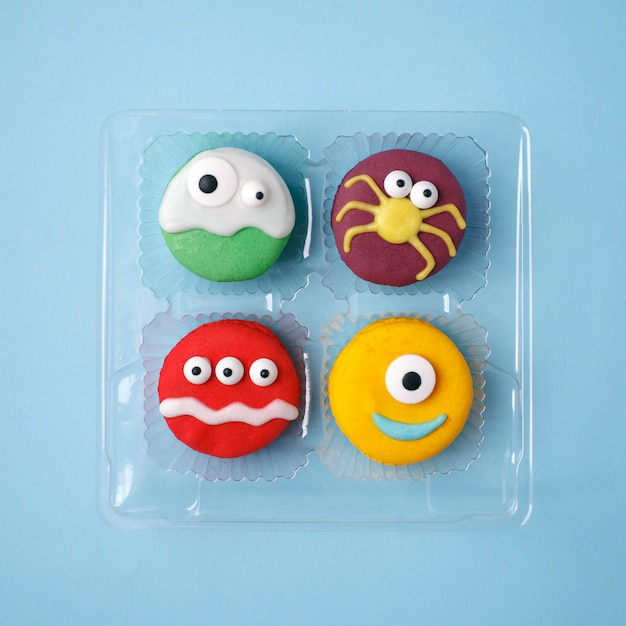 Heloween dessert: set of funny monsters, ghost, spider made of biscuits macaroon Premium Photo