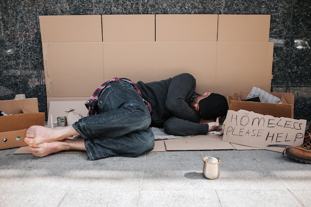 Helpless and defenceless man is lying on the cardboard on concrete floor and sleeping Premium Photo