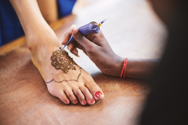 Henna artist (mehndi) painting the foot of women on the indian wedding day Premium Photo