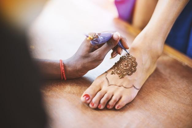 Художник хны (mehndi) рисует ногу женщин в индийский день свадьбы Premium Фотографии