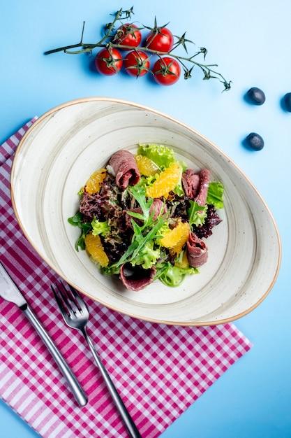 Herb salad with ham and orange slices Free Photo