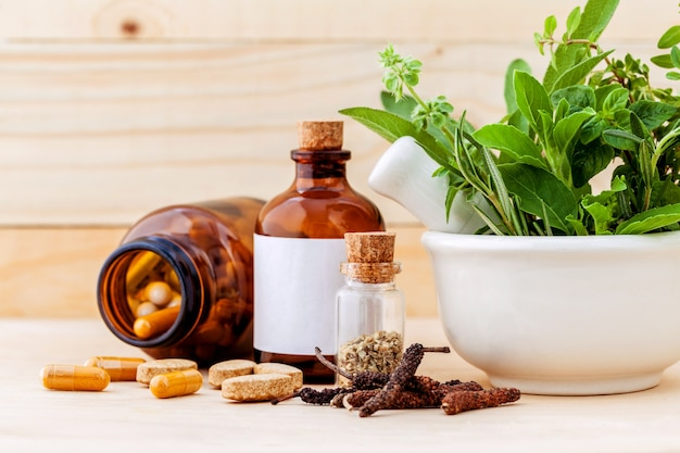 Herbal capsule on wooden background. Premium Photo