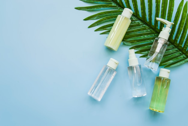 Herbal cosmetic product bottle on green leaf against blue background Free Photo