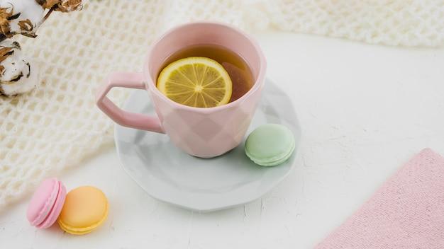 Herbal lemon tea with macaroons on white backdrop Free Photo