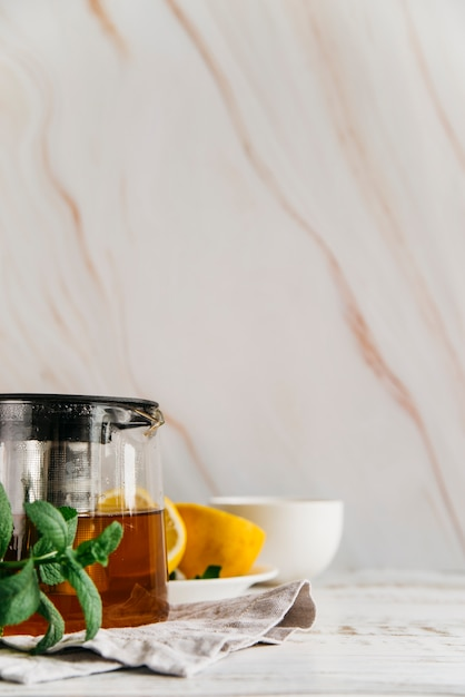 Herbal lemon tea with mint on textured backdrop Free Photo