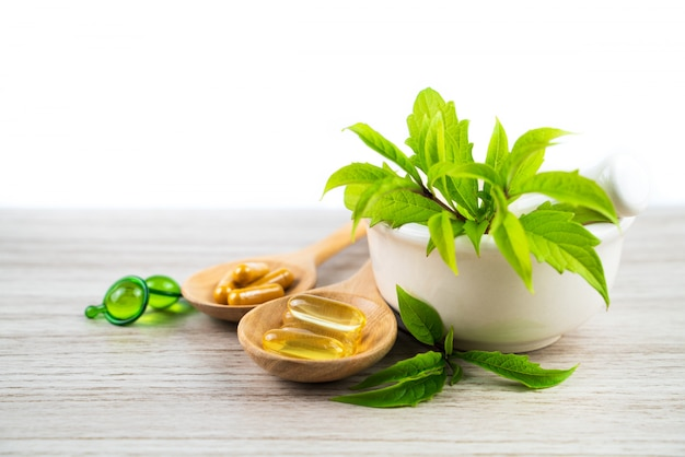 Herbal medicine from green leaf herb, capsule and vitamin on wood table Premium Photo