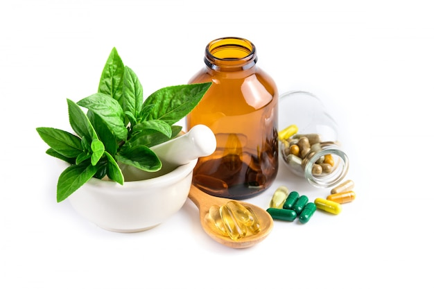 Herbal medicine from green leaf herb, pill, tablet, capsule, drug and vitamin in glass and wooden spoon Premium Photo