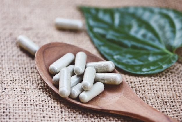 Herbal medicines / natural herb capsules on wooden spoon and green leaf on sack background Premium Photo