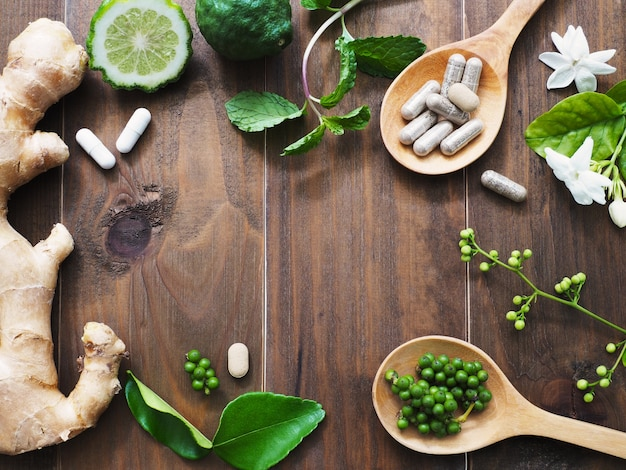 herbal pills in wooden spoon and herbs Premium Photo