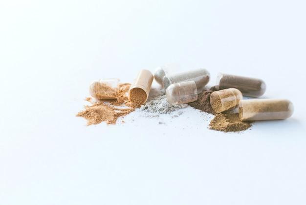 Herbal pills. open herbal capsules and powder on white background. Premium Photo
