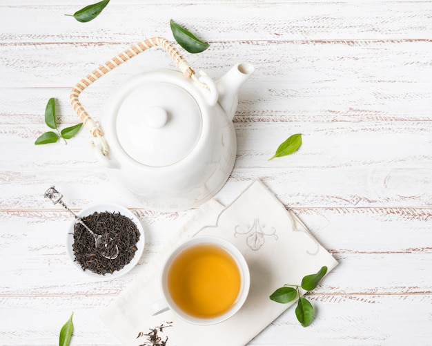 Herbal tea cup with dried herbs and teapot on white textured background Free Photo