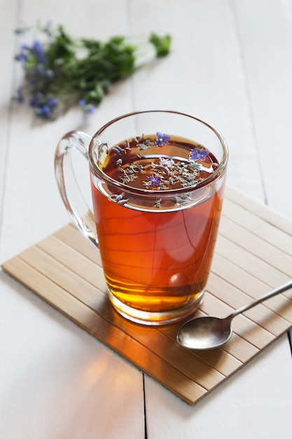 Herbal tea with blossoms in a glass Premium Photo