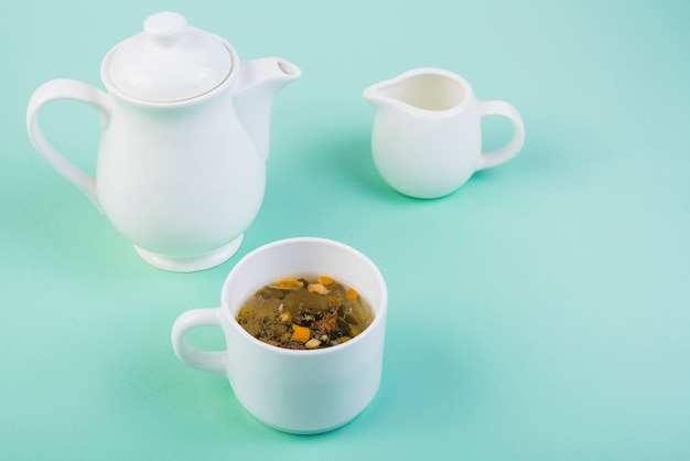 Herbal tea with crockery on turquoise background Free Photo